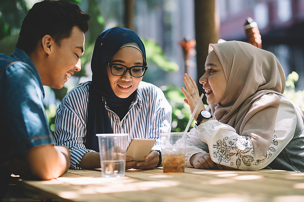 Three Malay Friends Talking To Reach Other While Looking Into Smart Phone Photograph by Chee Gin Tan