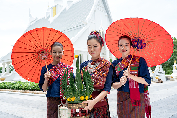 Three Thai girls dressed in traditional Isan traditional dress to go to the temple. Photograph by Sutiporn Somnam