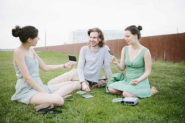 Three Young Adults Looking Their Instant Pictures Photograph by Fotografixx