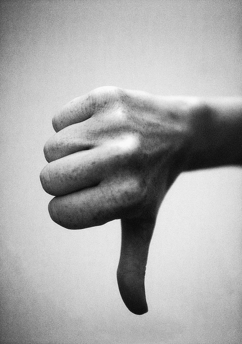 Thumb pointing down, close-up, b&w Photograph by Laurent Hamels