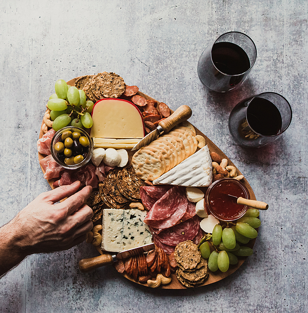Top view of hand taking food off charcuterie board on stone counter. Photograph by Cavan Images