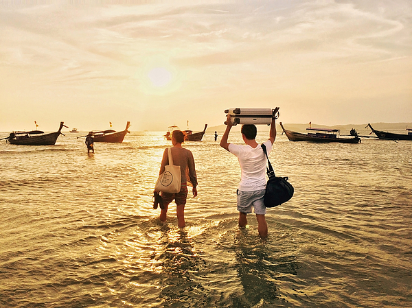 Travelling couple in Thailand walking in the ocean to the longtail boat with their luggage bags above the head Photograph by Alexander Spatari