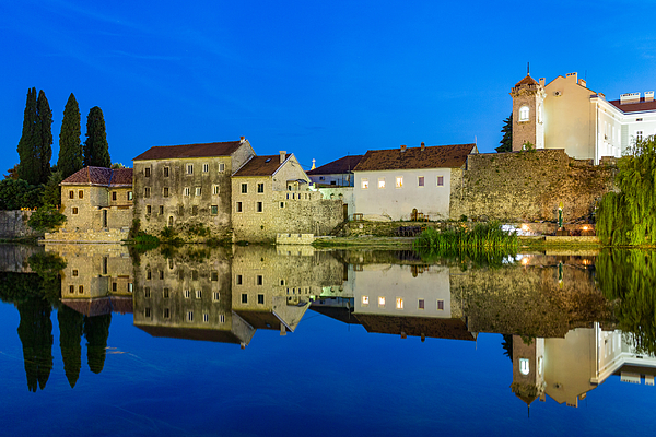 Trebinje reflected in the Trebišnjica river at night, Bosnia and Herzegovina Photograph by Frans Sellies