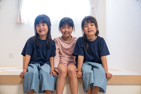 Twin Girls Sitting Together With Older Sister Photograph by Trevor Williams