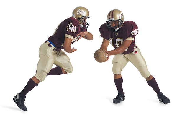 Two African American Football Players Wearing Red And White Uniforms Are Running Towards Each Other As One Prepares To Pass The Ball To The Other Photograph by Photodisc