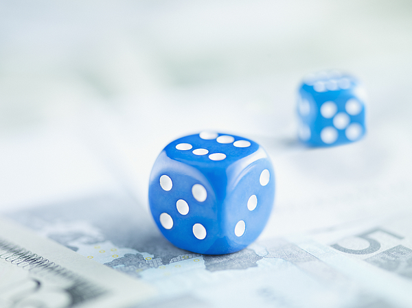 Two blue dice on pile of euro notes Photograph by Martin Barraud
