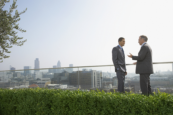 Two businessmen on rooftop talking, side view  Photograph by Justin Pumfrey