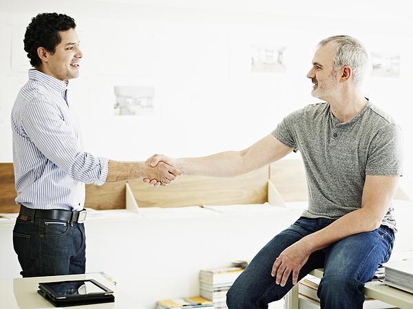 Two businessmen shaking hands in startup office Photograph by Thomas Barwick
