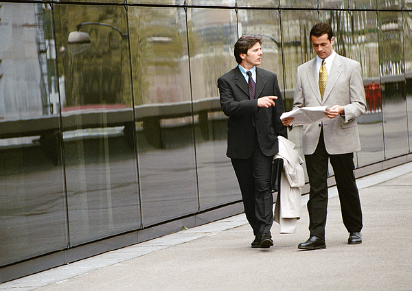 Two Businessmen Walking Along Sidewalk In Front Of Building Photograph by Eric Audras