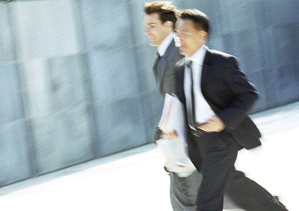 Two businessmen walking outdoors, blurred motion Photograph by Eric Audras