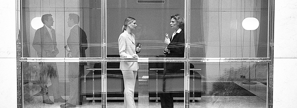 Two businesswomen behind large glass window, B&W Photograph by Teo Lannie