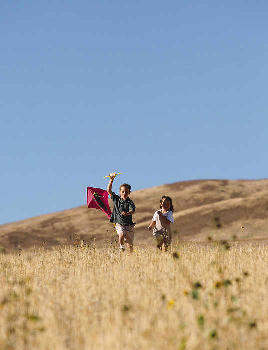 Two Children Run Through A Golden Field With A Kite Photograph by Photodisc