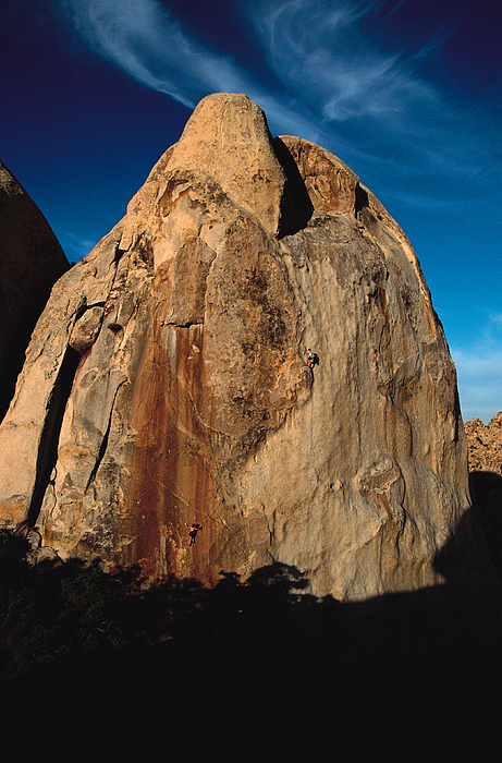 Two Climbers Are Scaling The Side Of A Large Rock Formation With The Sun Shining On The Face Of It And A Blue Sky In The Background Photograph by Rubberball