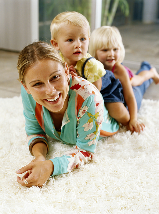 Two girls (21-24 months) on womans back, lying on rug, smiling Photograph by Kraig Scarbinsky