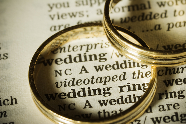 Two gold wedding bands on top of paper with the word wedding Photograph by JLGutierrez