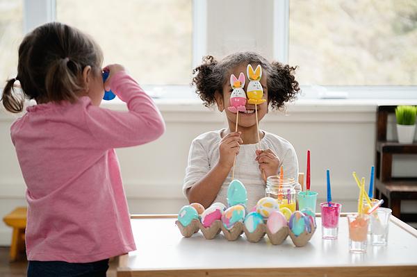 Two Little girls looking through Easter eggs. Photograph by Manonallard