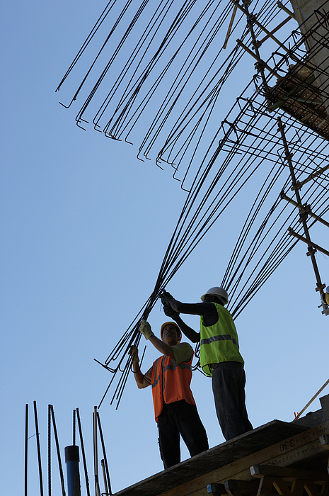 Two Male Construction Workers Stand on a Roof, Bending a Frame Into Position Photograph by Digital Vision.