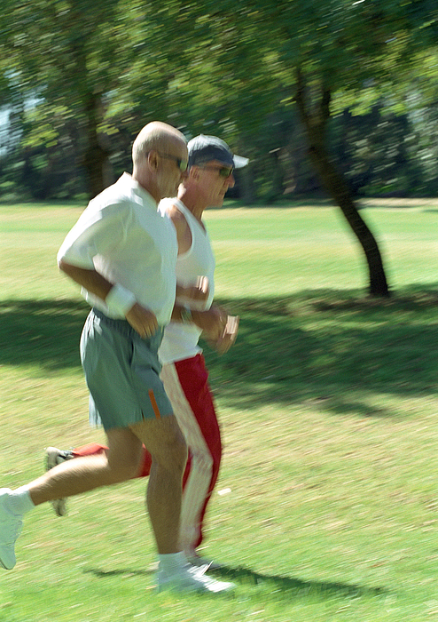 Two Mature Joggers In Park, Side View Photograph by Vincent Hazat