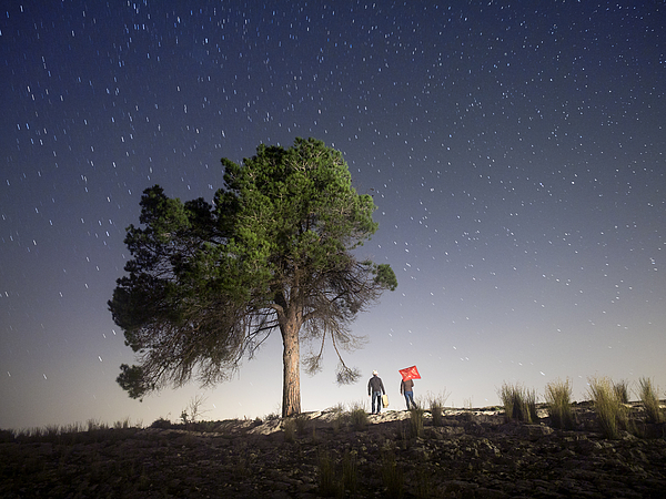 Two persons camiando with suitcases in the night Photograph by Jose A. Bernat Bacete