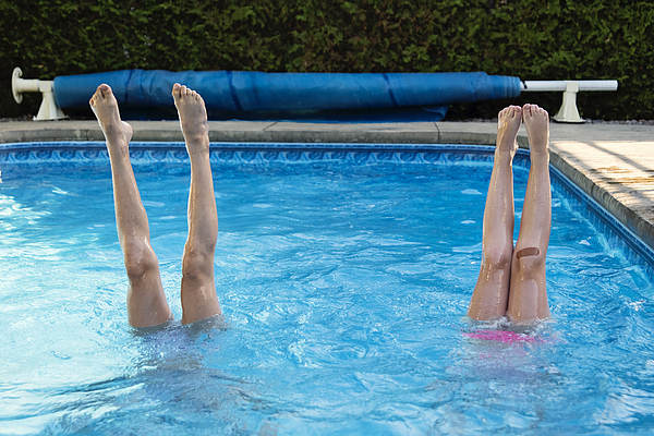 Two preteen girls legs standing up in pool. Photograph by Martinedoucet
