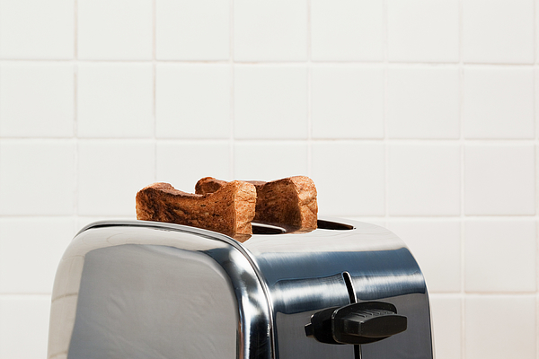 Two slices of toast in toaster Photograph by Image Source