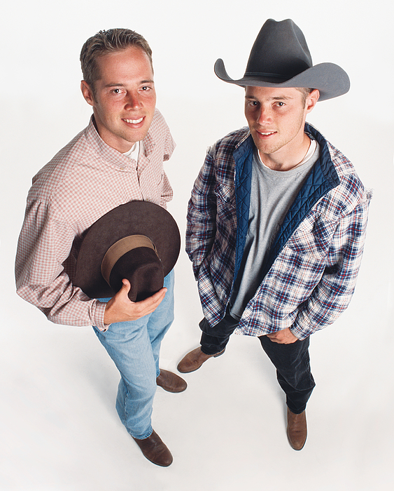 Two Young Adult Caucasian Cowboys Wearing Boots Are Standing Beside Each Other One Holding A Hat And One Wearing A Hat Photograph by Photodisc