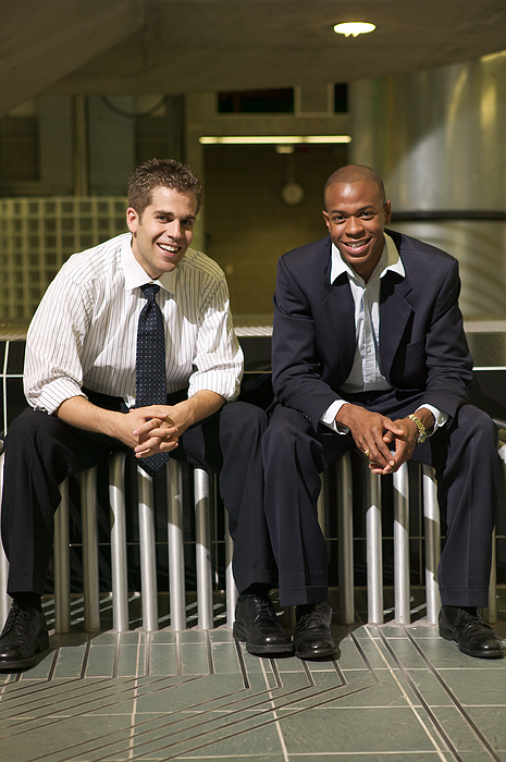 Two Young Business Men Sit And Smile On A Bench In Their Office Atrium Photograph by Photodisc