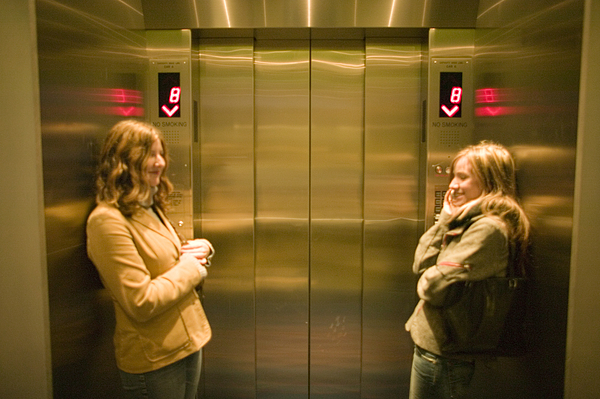 Two young women waiting in elevator Photograph by Photodisc