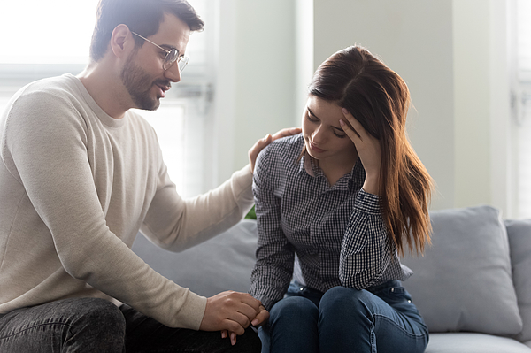 Unhappy stressed woman sitting on sofa with empathic husband. Photograph by Fizkes