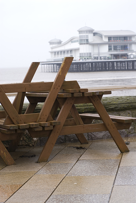 Upturned wooden tables at out of season seaside Photograph by Lyn Holly Coorg