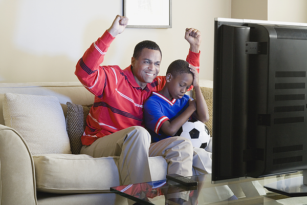 USA, California, Los Angeles, Father and Son (12-13) watching sports on tv Photograph by Rob Lewine