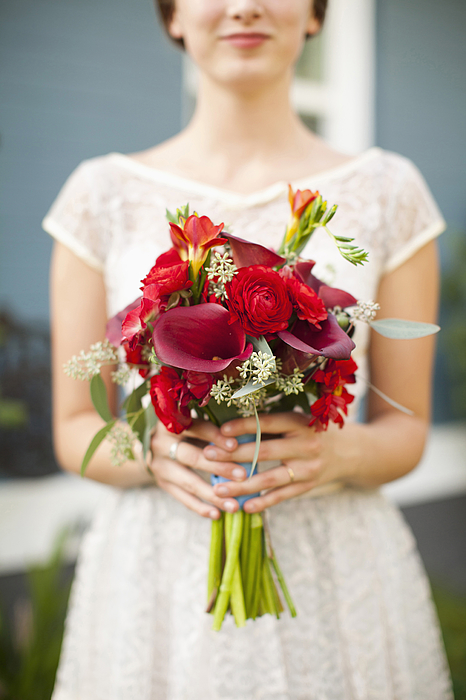 USA, Utah, Provo, Mid section of bride with bouquet in focus Photograph by Tetra Images - Jessica Peterson