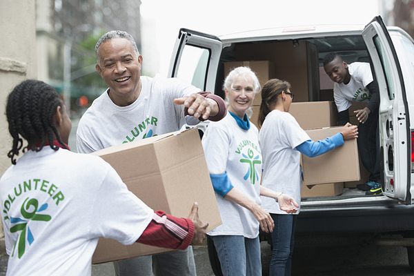 Volunteers passing cardboard boxes from delivery van Photograph by Jose Luis Pelaez Inc