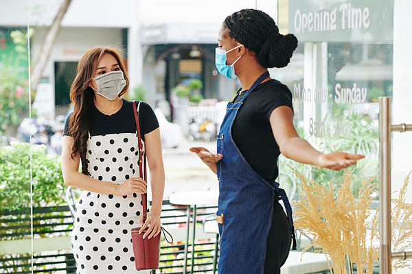 Waitress in medical mask inviting customer Photograph by DragonImages