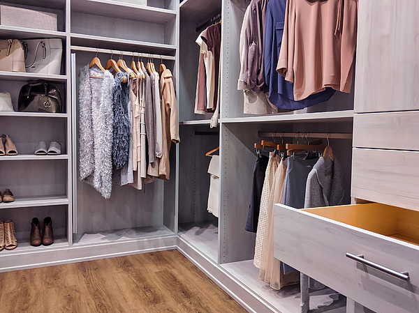 Walk In Closet With Clothes Hanging And Shoes On Shelving Photograph by Colleen Michaels