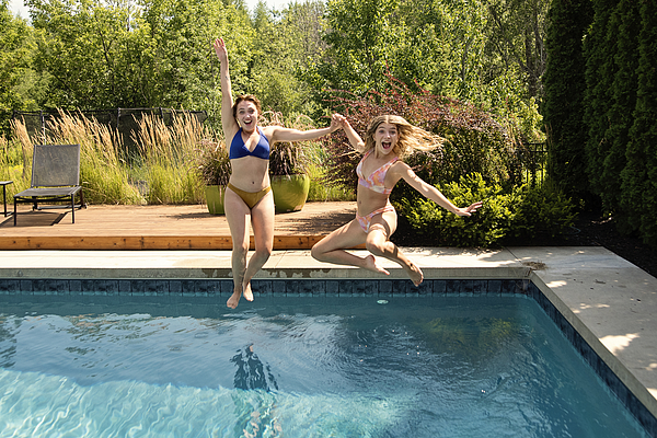 Water fun for two cousins jumping in backyard pool. Photograph by Martinedoucet