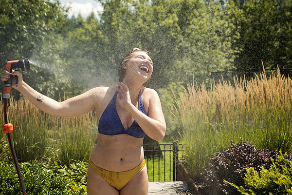Water fun for young woman in backyard. Photograph by Martinedoucet