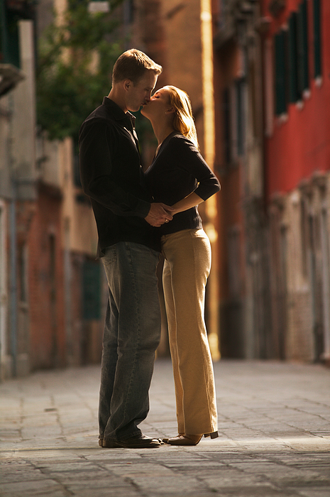 Wide Shot Of A Young Adult Couple As They Hug And Kiss On An Old Cobblestone Road Photograph by Photodisc