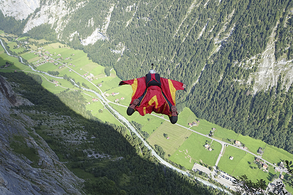 Wingsuit flier in airborne descent towards valley Photograph by Ascent Xmedia