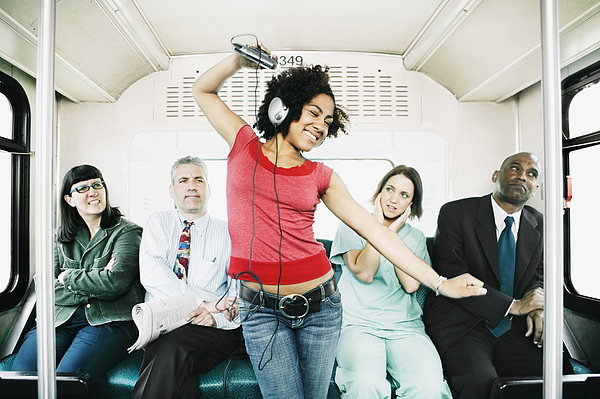 Woman annoying passengers by dancing on bus Photograph by Brand X Pictures