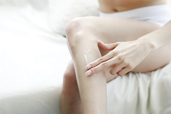 Woman Applying Body Lotion On Leg Photograph by Runstudio