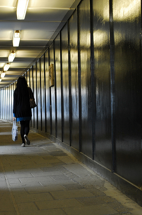 Woman carrying shopping walking through underpass Photograph by Lyn Holly Coorg