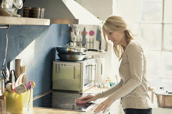 Woman Cleaning Kitchen Photograph by Simon Winnall