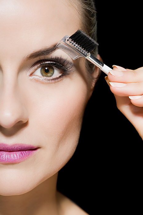 Woman combing her eyebrow Photograph by Image Source