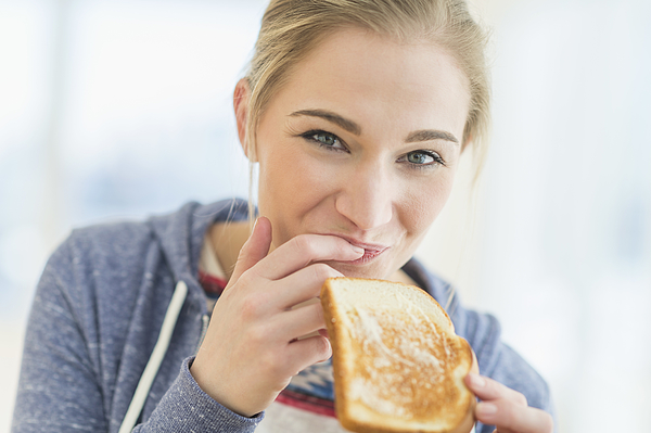 Woman eating toast, Jersey City, New Jersey, USA Photograph by Tetra Images