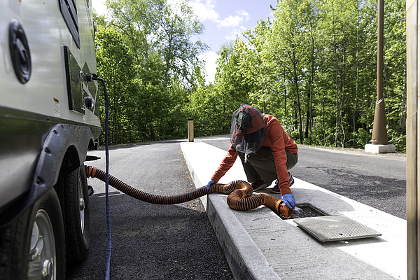 Woman Emptying RV Sewer After Camping Photograph by Onfokus