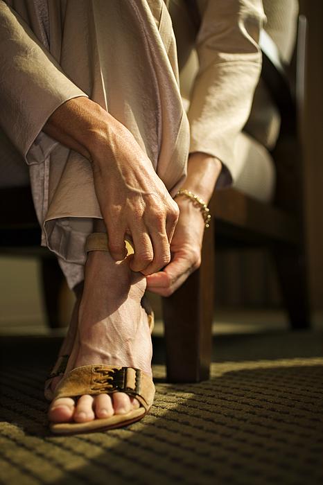 Woman fastening sandal Photograph by Thinkstock