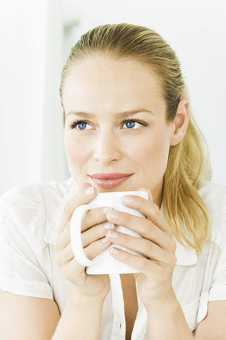 Woman holding mug, portrait Photograph by Pando Hall