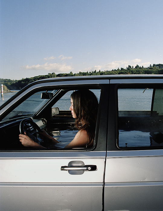 Woman in car filled with water, side view Photograph by Matthias Clamer