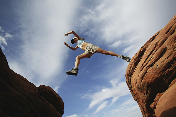 Woman jumping over rock ledge Photograph by Jupiterimages